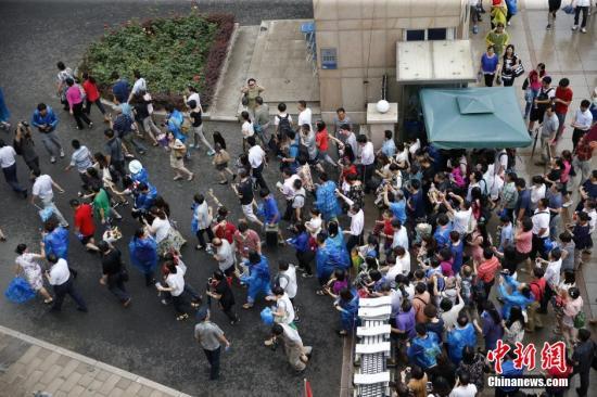 6月8日下午,北京人大附中考点,众多家长在北京高考最后一门考试结束后冲进学校内迎接考生。中新社发 张浩 摄