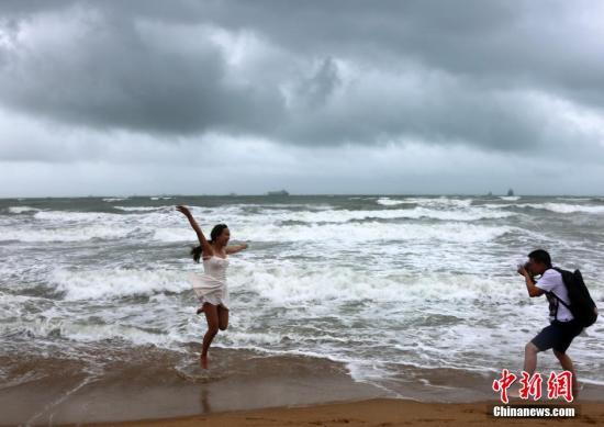 6月22日,海南三亚,游客在乌云密布、大浪翻滚的三亚湾游玩嬉戏,享受风雨带来的清凉。中新社发 尹海明 摄