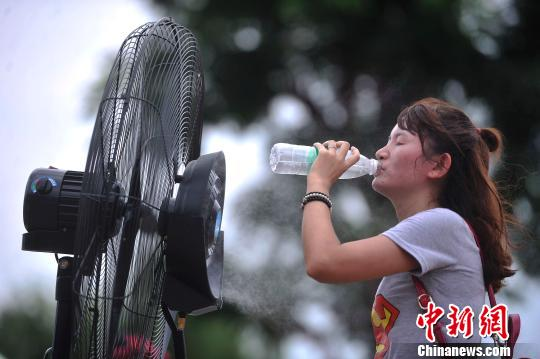 """喝水的""""说道""""也有很多。(资料图:一女士正面对着喷有水雾的电风扇喝水纳凉。 陈超 摄)"""