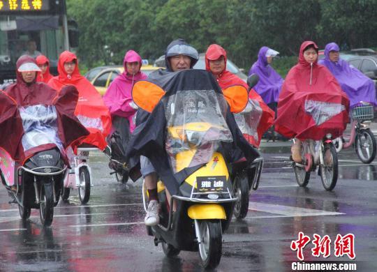 市民骑车在雨中的南京街头经过。李珂 摄