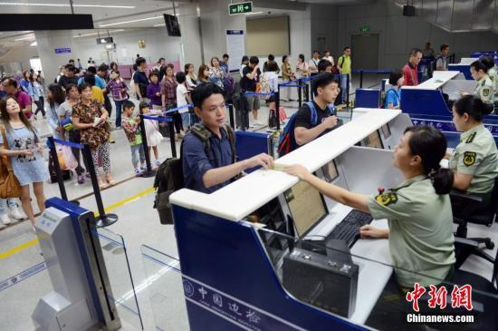 7月1日,搭乘MF880航班的旅客及台胞从台北桃园飞抵福州长乐国际机场办理入境手续。大陆对台湾同胞免签注政策7月1日起正式实施。台胞持有效台湾居民来往大陆通行证(台胞证)即可经开放口岸来往大陆并在大陆停居留,无需办理签注。中新社发 刘可耕 摄