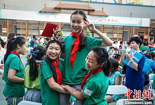 资料图:北京光明小学的两名毕业生抬着另一名同学合影。中新社发 张浩 摄