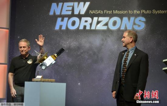 """资料图:""""新视野号""""飞掠冥王星,卫星模型被摆放在演讲台上。"""