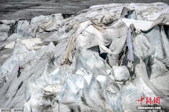 资料图:2015年7月14日,在瑞士阿尔卑斯山脉的罗纳冰川,一名女子在保护冰川的隔热材料附近进行冰上攀岩。瑞士罗纳冰川位于瑞士瓦莱州。瑞士壮美的冰川景观吸引着世界各地游客。受全球气候变暖影响,瑞士冰川不断消融。