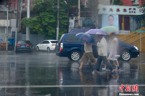资料图:北京街头民众在雨中行走。中新网记者 金硕 摄