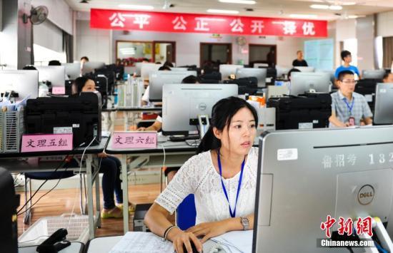 7月20日,持证工作人员确认考生录取信息。 中新社发 张勇 摄