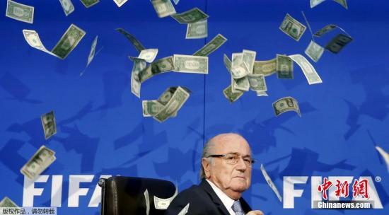 """当地时间7月20日,国际足联召开特别执委会,宣布特别选举大会将在2016年2月26日举行,届时将选出国际足联新主席。席间英国喜剧演员李-尼尔森突然乱入会场。他先是挥舞着钞票走向贪腐传闻缠身的国际足联主席布拉特,之后将一沓""""美钞""""砸向布拉特,纸币从空中散落,布拉特则露出惊慌表情,发布会就此中断。李-尼尔森随后被安保人员带走,据悉,所谓""""美元""""是假钞票。"""