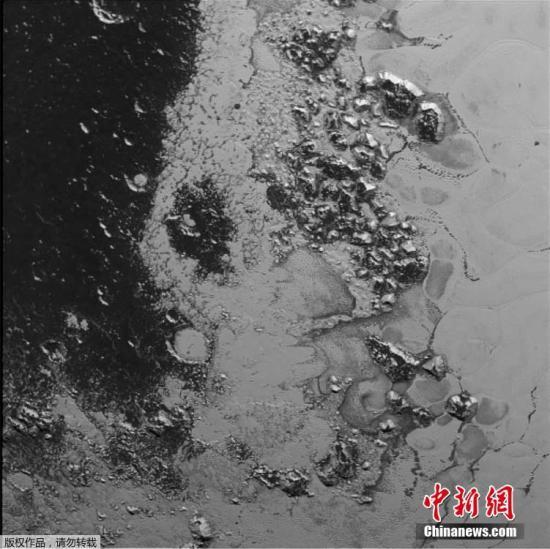 """资料图:""""新视野号""""拍摄的冥王星。位于冥王星南半球的巨大冰山的高度超过了3500米。"""