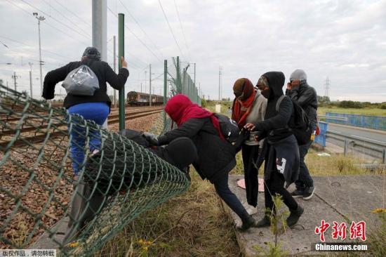 """当地时间7月29日,法国警方消息人士称,当地时间28日夜间,有至少1500名偷渡者试图从法国港口城市加莱一端冲击""""欧洲隧道""""(英法海底隧道),以通过隧道偷渡至英国。偷渡者冲击隧道的过程中有1人死亡。图为法国加莱附近的弗雷蒂安,偷渡者们正在穿越铁道旁的栅栏,进入铁道内。"""