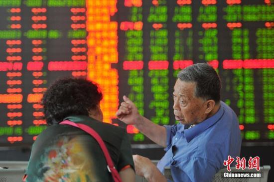 资料图:股民讨论股市。中新社发 韦亮 摄