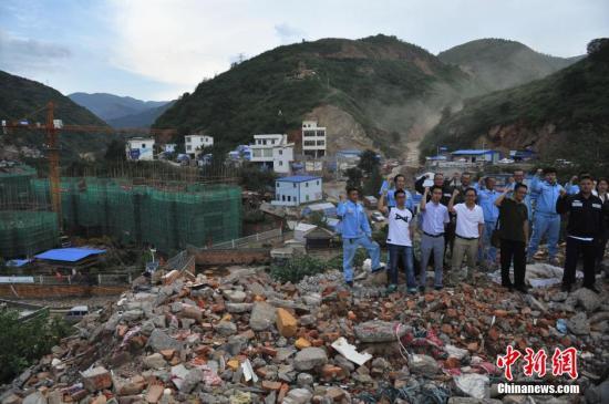 """来自云南电网的工作人员站在震中龙头山镇废墟前,高喊""""鲁甸加油""""。其身后是在最大安置点原址上修建中的新房。中新社发 任东 摄"""