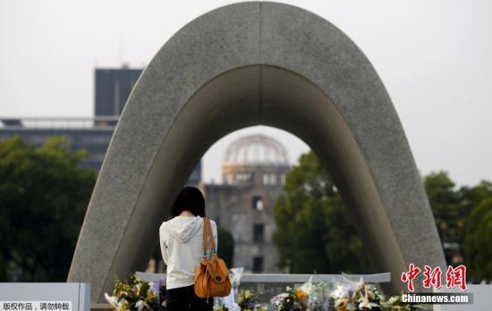 一名女士在和平纪念公园的纪念碑前为遇难者祈祷。