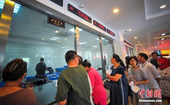 资料图:办证大厅内众多市民等待申请办理和领取护照。刘新 摄