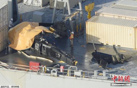 当地时间2015年8月12日,日本冲绳,美国海军舰甲板上的坠海直升机残骸。据日本第11管区那霸海上保安本部透露,北京时间12日中午12时左右,该海保部收到来自美军的情报称,一架美军直升机在冲绳附近海域坠海。坠海地点大约位于冲绳本岛中部附近的滨比嘉岛附近海域。据路透社消息,该直升机于训练期间坠海,事故造成6人受伤。