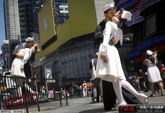 """资料图:美国纽约,情侣穿着水兵和护士的服装在时代广场接吻,重现""""胜利日之吻"""",纪念二战结束70周年。"""