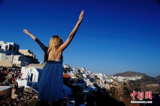 资料图:游客在圣托里尼岛度假。中新社发 陈文 摄