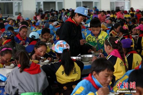 资料图:四川藏区一寄宿制小学的学生们正在食堂吃饭。陈运宙 摄