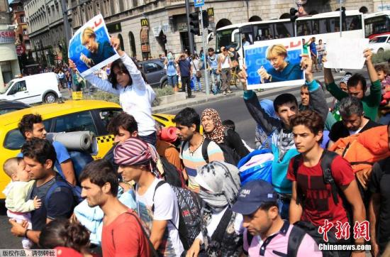资料图:难民们手持默克尔的照片,从匈牙利步行前往奥地利。