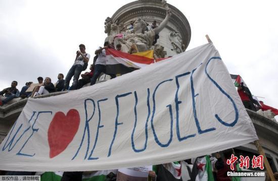 """巴百姓众打出横幅,下面写着""""咱们爱灾黎"""",欢送灾黎进入欧洲。"""
