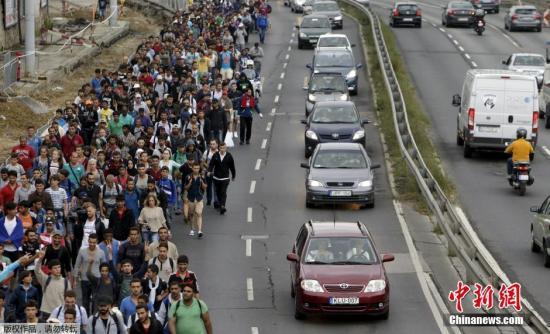 资料图:匈牙利境内难民徒步迁徙 前往奥地利与德国,难民们在高速路上行走,一度导致匈牙利首都交通瘫痪。
