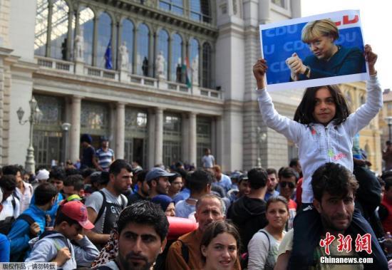 在匈牙利布达佩斯的一处火车站外,大量难民徒步前往匈奥边境,准备从奥地利前往德国。一名小女孩双手高举德国总理默克尔的照片。