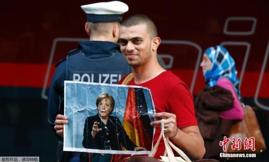 本地时刻9月5日,德国慕尼黑,不计其数的移民方法匈牙利和奥天时到达德国,来自叙利亚的灾黎手举德国总理默克尔的相片。德国总理默克尔此前示意,能够在不增税和作用估算的状况下对付新到达的灾黎潮。