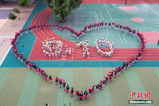 数百名小学生摆成巨型心形图形与9.10字样图案庆祝教师节。张云 摄