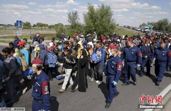 当地时间9月9日,移民试图冲破警察防线或翻越铁丝围栏离开位于匈牙利Roszke的安置点。