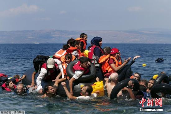 当地时间2015年9月13日,希腊莱斯博斯岛,承载叙利亚和阿富汗难民的一橡皮艇在靠近莱斯博斯岛100米远处泄气,当地民众和志愿者对难民进行了援助,难民们靠救生圈和游泳上岸。
