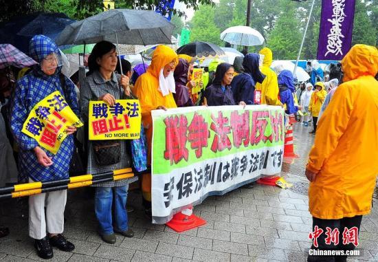 """随着安倍阵营强推以解禁集体自卫权为核心内容的安保法案最终过关的计划进入""""倒计时"""",日本民众的反安保抗议活动再度进入高潮。在之前彻夜抗议之后,9月17日白天,又有众多日本民众冒着大雨持续聚集在国会周边进行抗议活动。中新社发 王健 摄"""