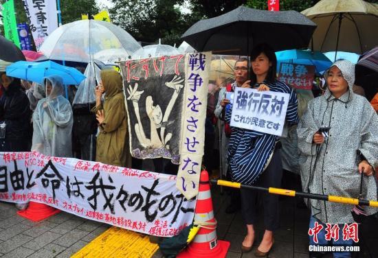 资料图:日本民众冒着大雨持续聚集在国会周边,抗议安倍强推安保法案。发 王健 摄