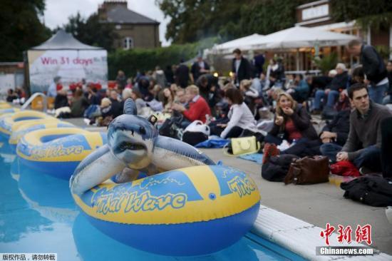一个大白鲨充气玩具静静呆在橡皮艇中,岸上坐满了等待电影开始的观众。