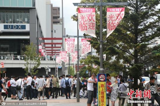 """资料图:日本东京,临近中国国庆长假,日本各大旨在招徕中国游客前来""""爆买""""的商家纷纷打出庆中秋、庆国庆的招牌。东京的池袋及秋叶原等中国客集中地,更是 商家""""暗战""""的集中地点。日本商家替中国人庆国庆节日的现象颇为有趣,也说明了日本商家已经深刻地了解了中国人的节庆习俗,并充分加以利用了起来。图片来源:CFP视觉中国"""
