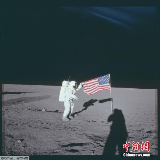 """1969年11月16日,阿波罗12号宇航员查尔斯・""""皮特""""・康拉德二世站在月球插着的美国国旗旁边。"""