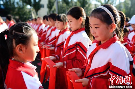 资料图:某销毁高年级同学为一年级新生佩戴红领巾。(图文无关) 中新社记者 刘文华 摄
