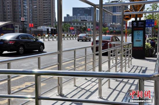 """首批启用的""""滴滴车站""""设有醒目的出租车停靠标识牌,还有乘客等待围栏区。 <a target='_blank' href='http://www-chinanews-com.cct010.com/'>中新社</a>发 周东潮 摄 图片来源:CNSPHOTO"""