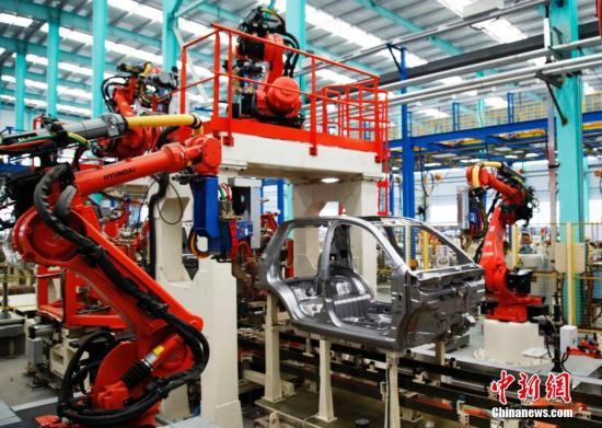 10月20日,在威海南海新区德瑞博新能源汽车制造有限公司车间内,红色的工业机器人正在进行冲压、焊装、总装等生产活动,标志着年产15万辆新能源汽车的生产线正式投产。该生产线采用全自动化生产工艺,在行业内处于先进水平,平均每3分钟生产一辆电动汽车。 刘昌勇 摄