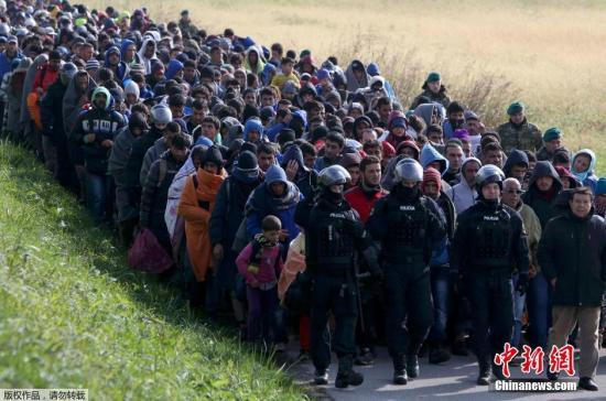 """当地时间10月20日,在斯洛文尼亚与克罗地亚边境城市多波瓦,斯洛文尼亚全副武装的军警""""护送""""从克罗地亚入境的难民。走在最前面的警察骑马开道,数千难民拍着长队一路步行前往难民所。自上周六以来,数千名寻求避难的人进入了斯洛文尼亚境内,迫使该国着手处理南部边境出现的难民激增的情况。斯洛文尼亚当局表示,至少有4000名难民于周二抵达该国境内,其中包括很多婴儿和年幼的孩子,再加上已经于周一抵达的大约8000名难民。"""