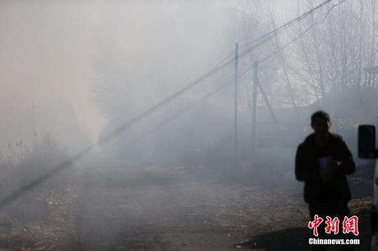 10月28日,吉林洮南,中科院东北地理所调查小组依据卫星拍摄到的火点追查秸秆焚烧情况。图为洮南市城外的甜水村,村民在焚烧稻草秸秆。孙立国 摄 图片来源:视觉中国
