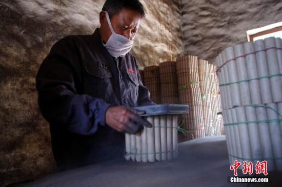 花炮制作的第四道工序:裝藥。這是花炮制作中最危險的工序,工人必須穿戴防靜電的特制衣服,使用塑料制成的裝藥模具,操作過程中必須隔離明火,小心謹慎。圖為裝藥工裝黑火藥裝入模具。 王昊陽 攝