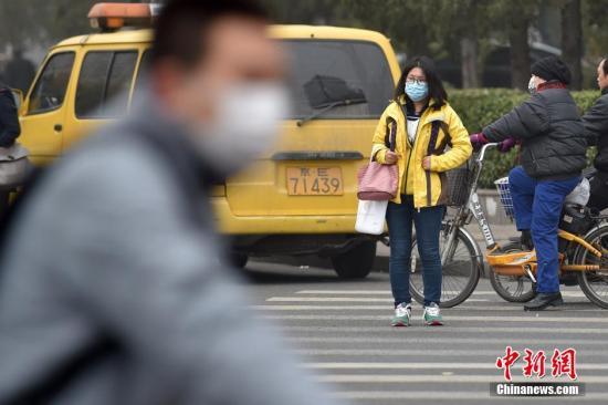 北京陌头市民佩带口罩出行。 中新网记者 金硕 摄
