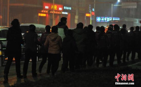 """2015年11月09日,辽宁省沈阳市,夜间雾霾严重持续未散,百人""""暴走团""""戴口罩现身街头。 图片来源:视觉中国"""