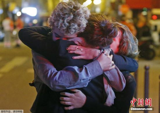 资料图:2015年11月,法国巴黎巴塔克兰剧院发生恐怖袭击事件。巴塔克兰剧院外,幸存者紧紧拥抱亲友。