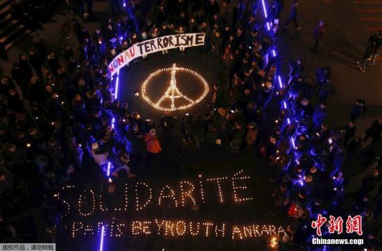 瑞士洛桑,本地大众用烛炬摆出埃菲尔铁塔的反战图象,为巴黎罹难者默哀。