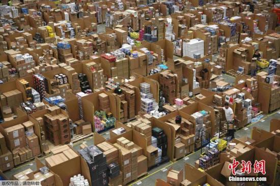 """除了实体店,网络电商也在""""黑五""""当天发力。图为英国Hemel Hempstead的一处亚马逊仓库内,工作人员正忙着给商品装箱。"""