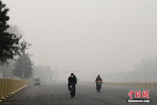 材料图:11月30日,北京,市民戴口罩骑行在雾霾中的长安街。中新社记者 盛佳鹏 摄