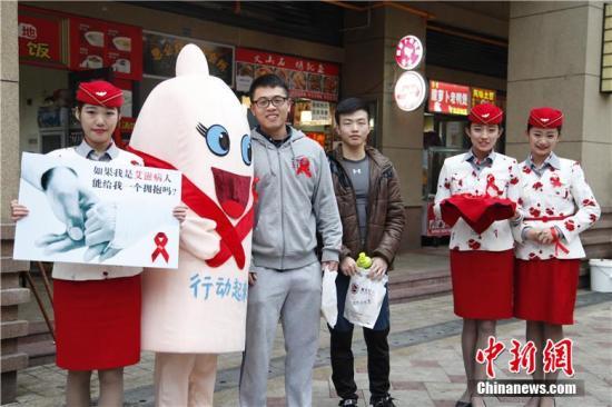 """12月1日上午,四川西南航空职业学院的10名准空姐、准空少来到街头,以""""艾滋病患者""""的身份,向过往的行人索要拥抱,并希望和她们交朋友,以此进行""""防艾""""宣传。毛成山 摄"""