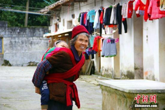 12月3日,在广西柳江县土博镇二中,老人正在照看孩子。在广西农村,很多农村教学点因学生数量不足等原因被撤并,孩子需到乡镇中心学校接受学前和义务教育,但因年龄小、离家远,27名家长在教育部门安排的免费住宿点照顾41个学生的起居。因青壮年劳动力外出务工,陪读家长多为孩子的母亲或爷爷奶奶。这一农村陪读现象也出现在广西桂林市灵川县三街镇、南宁市隆安县布泉乡、河池市都安瑶族自治县龙湾乡等地。 朱柳融 摄
