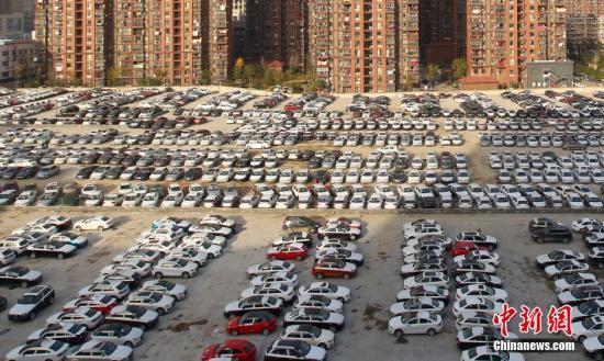 湖北武汉一小区楼前待开发的空地停了上百辆待售的新车。 图片来源:视觉中国