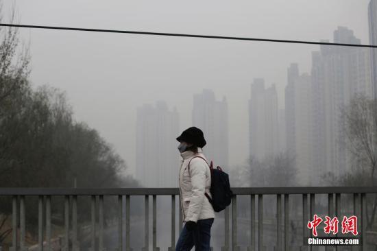 """12月8日,北京市民戴口罩出行。12月7日18时,北京市应急办发布,空气重污染预警等级由""""橙色""""提升为""""红色"""",即北京市于8日7时至10日12时将启动空气重污染红色预警措施,升级""""红色预警""""后,应急措施将有所加强,包括建议中小学、幼儿园停课,企事业单位根据空气重污染情况可实行弹性工作制等。此外,北京市全市范围内将实施机动车单双号行驶(纯电动车除外)。其中,北京市公务用车在单双号行驶的基础上,再停驶车辆总数的30%。 <a target='_blank' href='http://www-chinanews-com.cctv-asell.com/'>中新社</a>记者 李慧思 摄"""